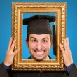 Graduate man looking through a frame — Stock Photo #13305260