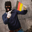 Man wearing a robber mask and holding airplane miniature and fla - Stockfoto