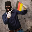 Man wearing a robber mask and holding airplane miniature and fla - 