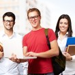 Group of young students against a university — Stock Photo #13305514