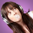 Portrait of young woman listening to music with bubble gum over — Stock Photo #13305555