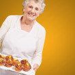 Portrait of cook senior woman holding a chocolate muffins tray o — Stock Photo #13305748