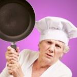 紫色の背景に隠れての上でパンをヒットしようとして怒っている年配の女性を調理します。 — ストック写真