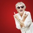 Portrait of senior woman doing rock symbol over red background — Stock Photo #13306479