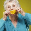 Portrait of senior woman holding a orange slice in front of her — Stock Photo