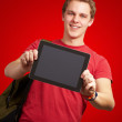 Portrait of young man holding a digital tablet over red backgrou — Stock Photo #13307476