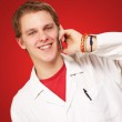 Portrait of young academic talking on mobile over red background — Stock Photo #13309097