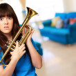 Stock Photo: Confused womholding trumpet