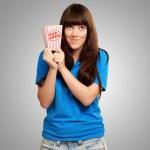 Girl holding empty popcorn packet — Stock Photo