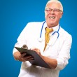 Happy Male Doctor Writing On Clipboard — Stock Photo #13309939