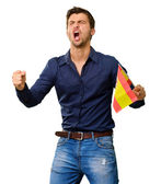 Man cheering and holding flag — Stock Photo