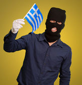 Man wearing robber mask and holding flag — Stock Photo