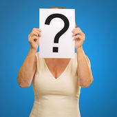 Mature woman holding question mark sign — Stock Photo