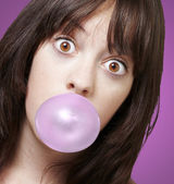 Young girl with a pink bubble of chewing gum against a pink back — Stock Photo