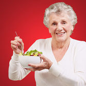Portrait of senior woman eating salad over red background — Stock Photo
