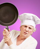 Cook senior woman angry trying to hit with pan over purple backg — Stock Photo