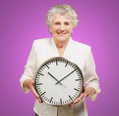 Portrait of a happy senior woman holding clock over purple — Stock Photo