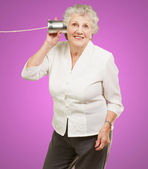 Portrait of senior woman hearing with metal tin can over pink ba — Stock Photo