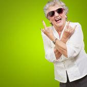 Senior vrouw dragen van een zonnebril doet funky actie — Stockfoto