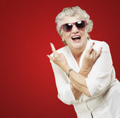 Portrait of senior woman doing rock symbol over red background — Stock Photo