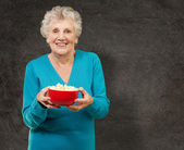 Senior woman holding popcorn — Stock Photo