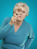 Portrait of senior woman looking through a magnifying glass over — 图库照片