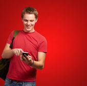 Portrait of young man touching mobile screen over red background — Stock Photo