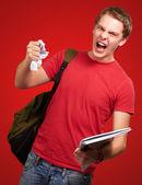 Uomo giovane studente arrabbiato un foglio di sgrossatura su sfondo rosso — Foto Stock