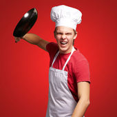 Portrait of angry young cook man hitting with pan over red backg — Stock Photo
