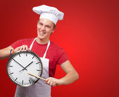 Portrét mladého kuchaře člověka ukazuje hodiny nad červeným pozadím — Stock fotografie