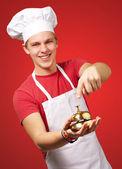 Retrato de hombre joven cocinero presionando una campana de oro sobre rojo backg — Foto de Stock