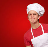 Young cook man having a idea over red background — Stock Photo