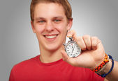 Portrait of a young man holding a stopwatch — Stock Photo