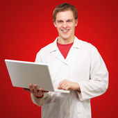 Portrait of young student holding laptop over red background — Stock Photo