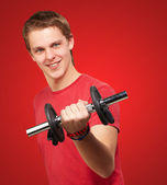 Portrait of young man with weights over red background — Stock Photo