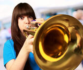 Portrait of a young girl blowing trumpet — Stock fotografie