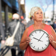 Senior Woman Holding A Clock — Stock Photo #13310012