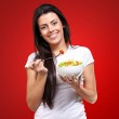 Portrait of healthy woman eating salad against a red background — Stock Photo #13310546
