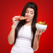 Portrait of young woman eating pizza and looking salad over red — Stock Photo #13310613