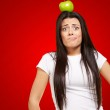 Portrait of young woman holding green apple on her head over red — Stock Photo #13310661
