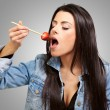 Portrait Of A Female Eating Strawberry With Chocolate Sauce - Stock Photo