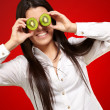 Portrait of young girl holding kiwi slices in front of her eyes — Stock Photo #13311033