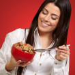 Portrait of healthy young woman eating cereals over red — Stock Photo #13311044