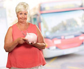 Woman Putting Coin In Piggy Bank — ストック写真