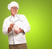 Chef Putting Coin In Piggybank — Stock Photo