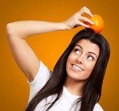 Retrato de mujer joven sosteniendo naranja sobre su cabeza sobre naranja — Foto de Stock