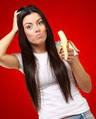 Eine junge frau, die eine banane essen — Stockfoto