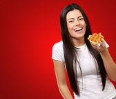 赤い背景の上のワッフルを保持している若い女性の肖像画 — ストック写真