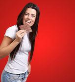 Ritratto di giovane donna mangiare cioccolato barra contro un rosso backgr — Foto Stock