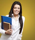 Młody student trzymania książek i uśmiechając się z pomarańczowym tle — Zdjęcie stockowe